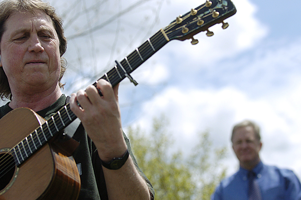 During gubernatorial candidate Patrick McGowan's campaign stop on Bangor's waterfront Monday afternoon, Mark Miller of East Millinocket performs the song &quotBack in Maine&quot that he co-wrote with Wayne Hendsbee. McGowan, a fan of Miller's, announced Monday that he has made the song his offical campaign song. Behind Miller is candidate Patrick McGowan. BANGOR DAILY NEWS PHOTO BY JOHN CLARKE RUSS