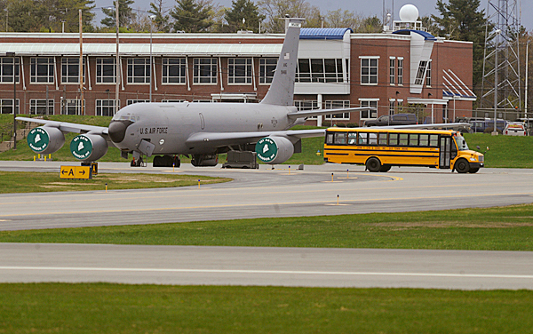 A spare school bus intended for passengers and crew passes an Air Force  KC-135  as the bus returns to Bangor International Airport's international arrivals building while assisting with the diverted Delta flight from Paris to Atlanta  Tuesday April 27, 2010. According to the Associated Press, U. S. officials say an American citizen on the flight claimed to have a fake passport and explosives in his luggage. According to Delta spokeswoman Susan Elliott there were 235 passengers and eight crew aboard the Airbus 330. Aftet the plane landed safely at 3:37 p.m.,  the passengers deboarded onto the tarmac at BIA and boarded buses to BIA's international arrivals building. BANGOR DAILY NEWS PHOTO BY JOHN CLARKE RUSS