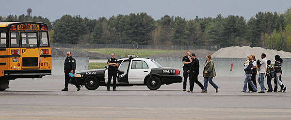 Bangor police officers watch as passengers from Delta flight 273 get off buses at the international arrivals building at Bangor International Airport after their flight from Charles de Gaulle International Airport in Paris was diverted due to a passenger claiming to have explosives in his luggage.  Hartsfield-Jackson Atlanta International Airport was the plane's final destination. BANGOR DAILY NEWS PHOTO BY KEVIN BENNETT