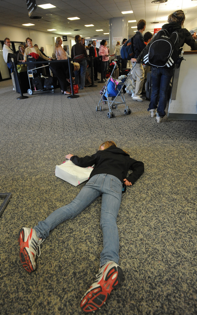Exhausted from her trip to Scotland and England, coupled with an 11-day delay due to the volcanic dust from Iceland, Rachel Watson, 10, of Vancouver, B.C., lays on the floor in front of the Delta ticket counter at Bangor International Airport on Wednesday, April 28, 2010. Watson's family was on board flight 273 from Paris to Atlanta, when it was diverted to Bangor on Tuesday due to a bomb threat by passenger Derek Stansberry of Riverview, Florida.  (Bangor Daily News/Kevin Bennett)