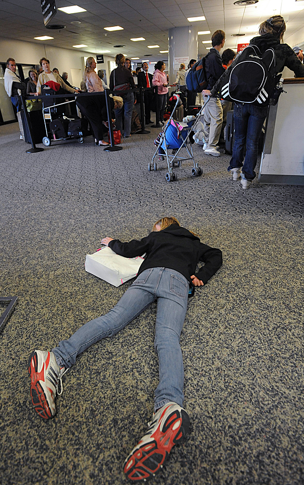 Exhausted from her trip to Scotland and England, coupled with an 11-day delay due to the volcanic dust from Iceland, Rachel Watson, 10, of Vancouver, B.C., lies on the floor in front of the Delta ticket counter at Bangor International Airport on Wednesday, April 28, 2010. Watson's family was on board flight 273 from Paris to Atlanta, when it was diverted to Bangor on Tuesday due to a bomb threat by passenger Derek Stansberry of Riverview, Florida. BANGOR DAILY NEWS PHOTO BY KEVIN BENNETT
