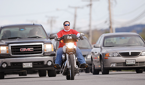 Jeri Leonard of Hampden is surrounded by larger vehicles as she cruises down Wilson Street in Brewer on her 2004 Harley-Davidson 1200 Sportster. BANGOR DAILY NEWS PHOTO BY JOHN CLARKE RUSS