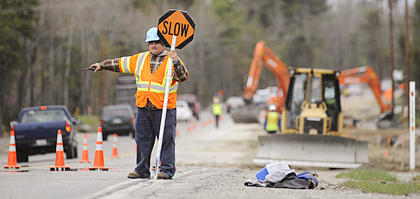 Robbie Lawrence of Bangor, a flagger with Maine Staffing Group's Project Flagging Inc., directs traffic around heavy equipment as road improvement work continued on the Ellsworth stretch of Route 1A Tuesday, April 27, 2010. BANGOR DAILY NEWS PHOTO BY JOHN CLARKE RUSS