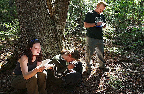 Deb Albert (from left) reads from the pages of a logbook found in a cache in Swan Lake State Park while Matt Fortin and Nick Bonzey write their message to be left in the geocache for others to read.  BANGOR DAILY NEWS PHOTO BY KEVIN BENNETT