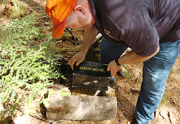 Mike Marino prepares to open a cache after finding it in a hollowed-out log in one of Bangor's public parks on Monday, April 26, 2010. Marino is an avid geocacher, who hides and posts his caches in the Bangor area at Geocaching.com.  BANGOR DAILY NEWS PHOTO BY KEVIN BENNETT