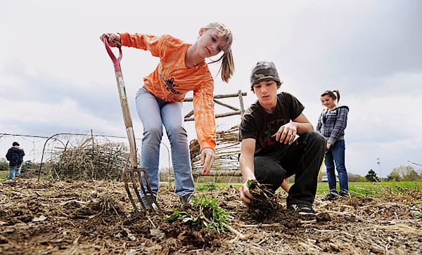 Desi Dodd, left, and Dakota Walker, center, remove weeds from the student garden at Troy Howard Middle School in Belfast on Thursday April 29, 2010. The Garden Project at the school aims to grow flowers, vegetables and herbs while teaching area youngsters about science and nutrition. Desi said her favorite part of working in the garden is &quotjust being outside.&quot  BANGOR DAILY NEWS PHOTO BY KEVIN BENNETT