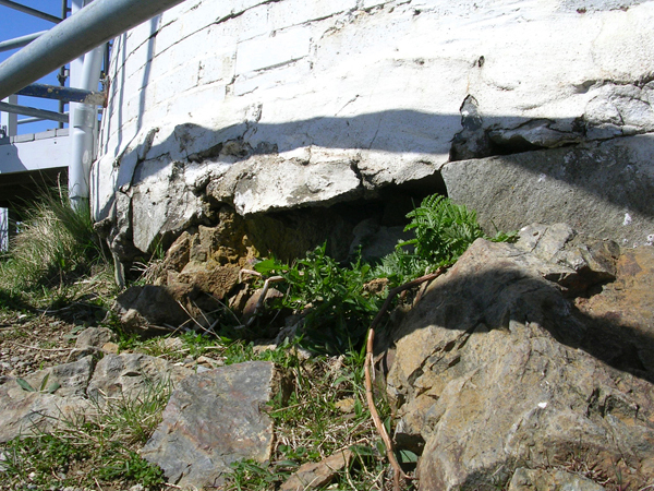 Owls Head Lighthouse is getting more than $248,000 in repairs this summer. The weather is responsible for battering the tower. (Bangor Daily News/Heather Steeves)   The rock foundation the Owls Head Lighthouse was built on has crumbled and leaves gaps. This is one of several repairs the lighthouse tower will undergo before July this year.(Bangor Daily News/ Heather Steeves)