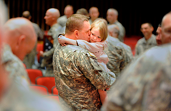 Lt. Col. Blair Tinkham of Orrington hugs his daughter, thre-year-old Tilly Tinkham at the conclusion of  Saturday's Freedom Salaute Ceremony for the 286th Combat Sustainment Support Battalion, Maine Army National Guard. The event took place at Peakes Auditorium in Bangor, Maine. The ceremony honored  Lt. Col. Tinkham  and 80 other soldiers in the battalion, their families, as well as community members who provided support during the soldiers' one-year deployment to Afghanistan. BANGOR DAILY NEWS PHOTO BY JOHN CLARKE RUSS