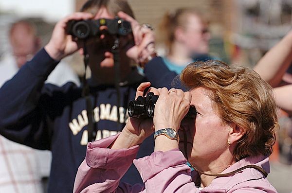 Olga Russell, foreground, of Bangor, uses binoculars to look for her son Dmitry Setrakov on board the Maine Maritime Academy training ship State of Maine shortly before it leaves Castine on a two-month training cruise. Gary Campbell of Hermon, background, also looks for his son, Kaleb, who is also aboard the ship. MMA's annual 60-day training cruise includes port visits at:  Marseille, France, May 19-22; a bunker (fuel) port call at Gibraltar, May 24-26; Kiel, Germany, June 1-4; Portsmouth England, June 7-10; and Portland, Maine, June 20-23. BANGOR DAILY NEWS PHOTO BY KEVIN BENNETT