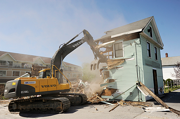 Joel Butler, owner of Holden-based J.E. Butler LLC, uses an excavator to raze the former Coffee Pot sandwich shop on State Street in Bangor Tuesday morning, May 4, 2010. BANGOR DAILY NEWS PHOTO BY JOHN CLARKE RUSS