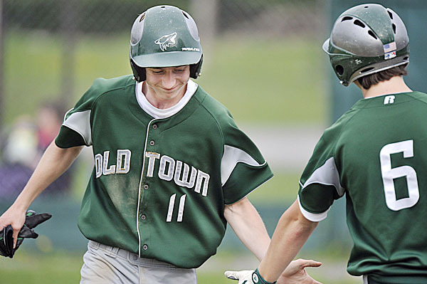 Old Town's Casey Estes ,(11), gets a congratulatory low-5 from teammate Shane Nadeau, (6), after scoring in the third inning of their game versus Hermon at Old Town , Tuesday, May 4, 2010. BANGOR DAILY NEWS PHOTO BY MICHAEL C. YORK