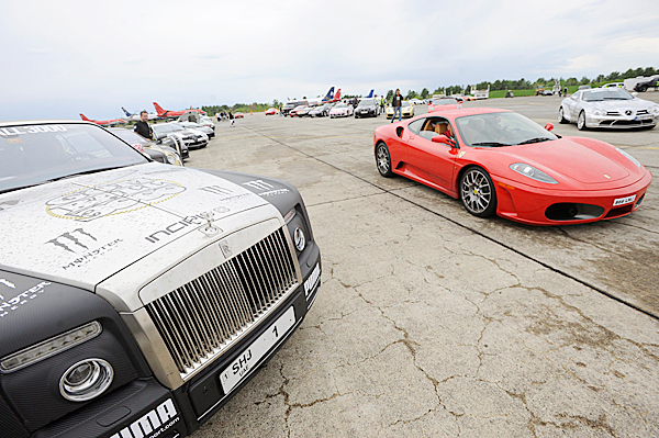 A rally driver cruises his Ferrari (right) past a competitor's Rolls Royce (left) after the rally teams' translatlantic flights arrived at Bangor International Airport Tuesday afternoon. BANGOR DAILY NEWS PHOTO BY JOHN CLARKE RUSS