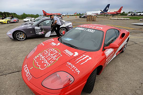 A Gumball 3000 road rally driver changes into his driving shoes shortly before getting into his high-performance rally car which was flown with other competitor cars to Bangor International Airport Tuesday . BANGOR DAILY NEWS PHOTO BY JOHN CLARKE RUSS