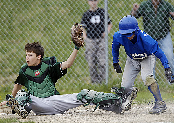 Howler's catcher Logan Jipson, (6), holds the ball high after tagging out Stearn's Dylan Bouchard ,(7), at the plate in the fifth inning of their game in Howland, Wednesday, May 4, 2010. BANGOR DAILY NEWS PHOTO BY MICHAEL C. YORK