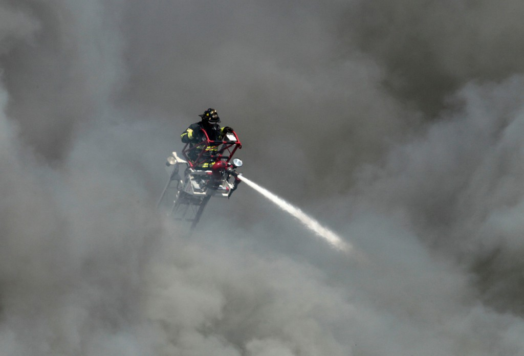 Thick, black smoke billows around a firefighter on a ladder as he pours water on a three-alarm fire at the former Jordan Meats building, Thursday, May 6, 2010, in Portland, Maine. The plant  was in the process of being demolished. (AP Photo/Robert F. Bukaty)