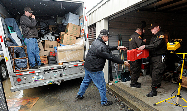 Law enforcement officials from the Pictataquis County Sherriff's office, the Greenville Police and the Maine Emergency Management Agency unload alledgedly stollen items from a storage unit in Shirley Thursday afternoon.  The unit was rented by Bruce Moore who recently lived in Greenville and has three outstanding warrants against him in Maine. BANGOR DAILY NEWS PHOTO BY GABOR DEGRE