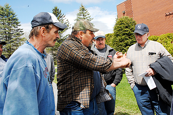 er Troy Taggart (second from left) makes a point on new state regulations impacting the use of bonded foreign workers in the Maine woods with fellow woods workers Mark McBreairty (left), Bobby Hafford (third from left) and Bobby McBreairty.   JULIA BAYLY PHOTO