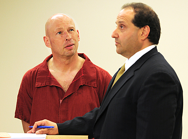 Horst Wolk, left, listens as a German interpreter translates for him while his attorney, Joe Baldacci, listens during his initial appearance on Friday, May 7, 2010 at the Penobscot Judicial Center in Bangor. Wolk is charged with attempted murder in connection with the Wednesday stabbing of his wife at Husson University.  BANGOR DAILY NEWS PHOTO BY KEVIN BENNETT