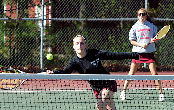Bangor High School's Michaela Whitney (left) charges the net as her partner Adriana Capuano looks on during their 1st doubles match against Brewer High School's Tonya Carlson and Kim Thorne in Bangor Friday afternoon.  Bangor won the match 6-1/6-1.  BANGOR DAILY NEWS PHOTO BY GABOR DEGRE