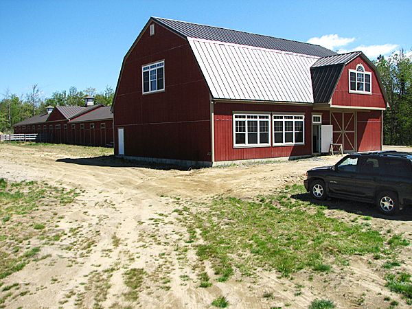 This 32-stall horse barn is the centerpiece of a roughly 130-acre property in Ellsworth that was sold Friday at a foreclosure auction for $401,000. The property, formerly known as Breezy Maples Farm, used to be owned by Eric S. Murphy Jr., a former mortgage broker who is facing criminal charges in Hancock County of stealing more than half a million dollars from investors in his business.  BANGOR DAILY NEWS PHOTO BY BILL TROTTER