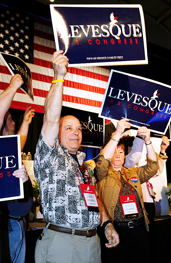 Delegate Jeffrey Clarke waves a sign as congressional candidate for the 2nd district Jason Levesque speaks Friday, May 7, 2010, at the opening day of the Maine Republican State Convention in Portland, Maine. Levesque is challenging incumbent Rep. Mike Michaud.  AP PHOTO BY JOEL PAGE
