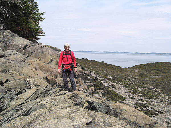 Brad Viles explores the rocks around the east shore of Horan Head, with Cobscook Bay in the background. The East Shore Trail is one of many trails in the   BRAD VILES PHOTO  05.08.10