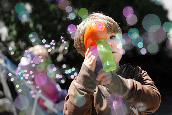 During lunchtime Monday, Bryleigh Woodbury (cq), 5, of Orono uses a bubble gun to disperse bubbles with a dozen or so others, mostly grown-ups,  at West Market Square in Bangor. Accompanied by her dad, Robert Woodbury  and her two-year-old sister Kaycee Woodbury, they were part of a whimsical Twitter &quotflashmob&quot social networking event that took advantage of Monday's pleasant weather. BANGOR DAILY NEWS PHOTO BY JOHN CLARKE RUSS