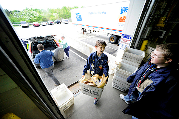 Nine-year-old Brandon Adams (center), a Bear Cub Scout with Bangor Cub Scout Pack 6, and Jacob DuBose (right), 12, helped unload mail bins filled with donated food items into the United Postal Service's Eastern Maine Processing & Distribution Facility in Hampden Saturday, May 8, 2010. Helping them (in background on left) was Isaac Mann, director of Seeds of Hope Food Pantry in Bangor as well as other volunteers. By the end of the day the food was ditributed to area food banks, pantries and shelters. The annual &quotStamp Out Hunger&quot food drive, purported to be the nation's largest one-day food drive, is organized by the National Association of Letter Carriers.   BANGOR DAILY NEWS PHOTO BY JOHN CLARKE RUSS
