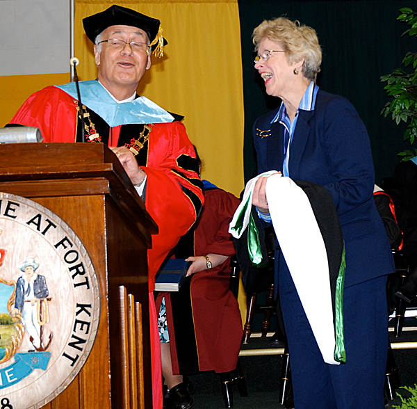 University of Maine at Fort Kent President Dr. Richard Cost shares a laugh with Anne Woodbury during the UMFK commencement exercises Saturday. Anne Woodbury accepted a posthumous honorary Doctorate of Humane Letters on behalf of her husband, the late Dr. Robert Woodbury, former?University?of Maine System chancellor.  JULIA BAYLY PHOTO