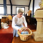 Parishioner Sara Lindsay placed her donated baby food items next to the baptismal font  before Sunday's service at St. James' Episcopal Church in Old Town. The Outreach team of the church sponsored a baby item drive and baby shower for the Indian Women's Mission on Mother's Day Sunday.  BANGOR DAILY NEWS PHOTO BY JOHN CLARKE RUSS