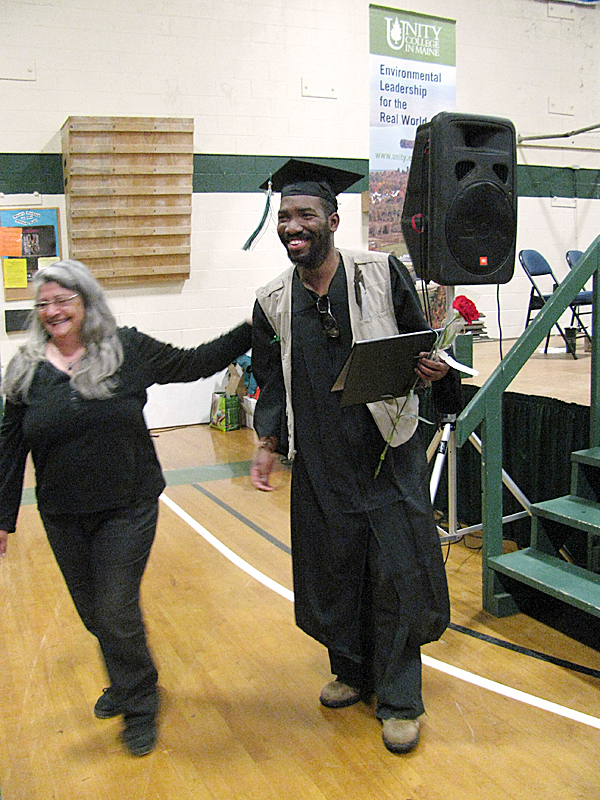 UNITY - Unity College graduating senior Zamir Twiggs of Philadelphia, beams Saturday afternoon after he received his diploma and then a flower from former college employee Cheryl Montana. &quotI'm ecstatic,&quot Twiggs said after the commencement ceremony. &quotI'm bouncing for joy,&quot   BANGOR DAILY NEWS PHOTO BY ABIGAIL CURTIS