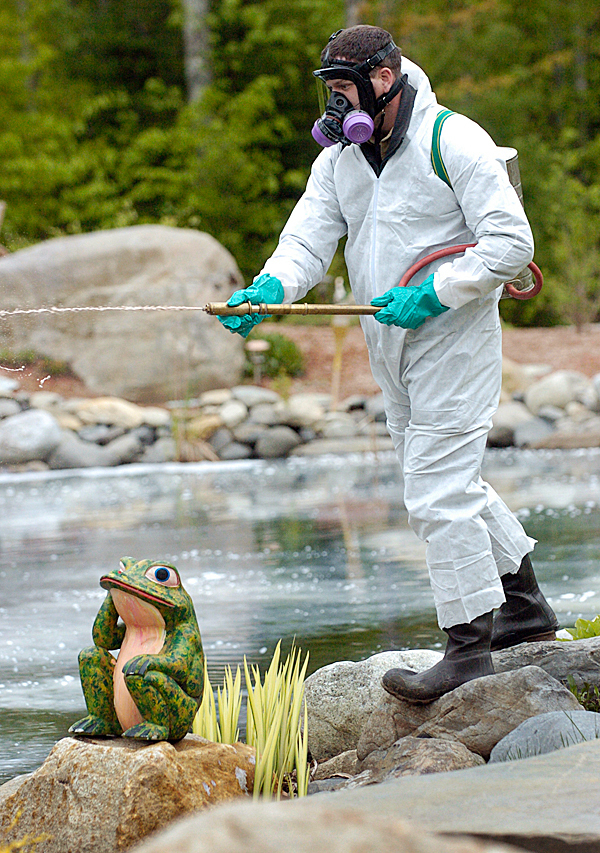 Wearing protective garb, Jason Seider, a fisheries research biologist with the Maine Dept. of Inland Fisheries and Wildlife's Bangor office, uses an backpack fire pump to spray a plant-based chemical called rotenone in a fish pond at Wildwood Trailside Cabins in Brownville, Maine. Seider and other DIF&W officials visited the site to remove and relocate some of the goldfish in the man-made outdoor pond there because it is illegal to have exotic/noxious invasive fish species in outdoor ponds in Maine. BANGOR DAILY NEWS PHOTO BY JOHN CLARKE RUSS