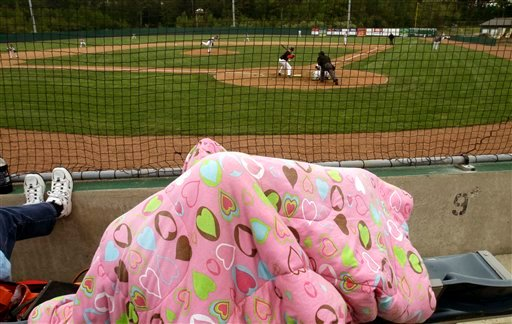 Chilly fans huddle under a blanket at one of the first baseball games  played at the newly revitalized park in Old Orchard Beach, Maine, on Monday, May 10, 2010. The Ballpark was home to the Triple-A Maine Phillies back in 1988 and is currently hosting the United States Collegiate Athletic Association 2010 National Baseball Tournament.( AP Photo/Pat Wellenbach)