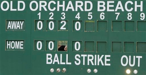 Colby Brown, of Old Orchard Beach, scoreboard keeper for the day, peers out to watch the action during one of the first baseball games  played at the newly revitalized park in Old Orchard Beach, Maine, on Monday, May 10, 2010. The Ballpark was home to the Triple-A Maine Phillies back  in 1988 and is currently hosting the United States Collegiate Athletic Association 2010 National Baseball Tournament.( AP Photo/Pat Wellenbach)