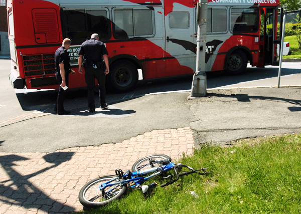 Bangor police inspect the side of a city BAT bus on Tuesday morning, May 11, 2010, after a man riding a bicycle with no brakes lost control and collided with the bus at the intersection of Main and Union streets. The man was transported to EMMC by ambulance for evaluation.  (Bangor Daily News/Kevin Bennett)