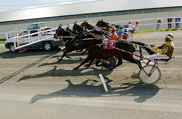 Drivers and their horses get ready to leave the gate as they follow the pace truck to the start of race three on the opening day of harness racing at Hollywood Slots Hotel & Raceway Tuesday afternoon, May 11, 2010. BANGOR DAILY NEWS PHOTO BY JOHN CLARKE RUSS