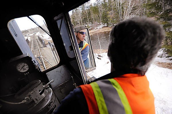 Engineer Rick Cameron of the Montreal, Maine & Atlantic Railway looks in his rearview mirror to check out cars behind him as he reverses Engine 100 at Squapan station recently. Engine 100 was built in 1957.  BANGOR DAILY NEWS FILE PHOTO BY JOHN CLARKE RUSS