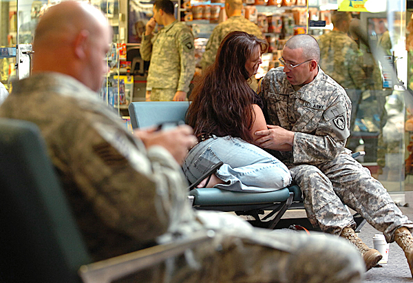 Mike Francis, right, of Old Town, cuddles with a friend at the Bangor International Airport on Thursday, May 13, 2010. Francis, a member of the Maine Army National Guard's 1136th Transportation Company, along with about 170 soliders who stopped  at BIA for refueling were greeted by family  and friends before their 10-month deployment to Afghanistan. BANGOR DAILY NEWS PHOTO BY KEVIN BENNETT