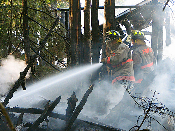 Firefighters spray water on smoldering debris at a Sullivan house fire late Thursday afternoon. No was was injured in the blaze, which destroyed a vacant home and spread slightly into nearby woods. Sullivan Fire Chief Mike Hiser said he does not know who the owners are or if the building was insured. He said he expects to call the State Fire Marshal's Office to investigate the cause of the blaze. BANGOR DAILY NEWS PHOTO BY BILL TROTTER