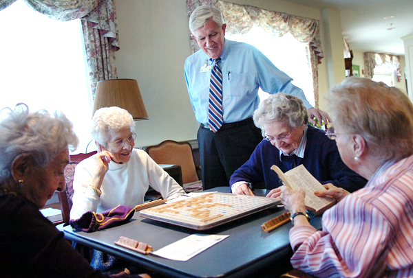 Nelson Durgin, Executive Director of the Phillips-Strickland House in Bangor, (standing) visits with the home's Thursday afternoon Scrabble group Thursday, May 13, 2010 which includes (from left) Aline Cobe, Teile Benson, Miriam &quotBunty&quot Hastings and Dorothy &quotDotty&quot Johnson. Durgin is retiring after more than 15 years at the independent living and residential care facility for seniors. (Bangor Daily News/Bridget Brown)