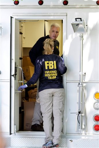 FBI investigators speak at the back door of a van outside a home at 39 Waverley Avenue, in Watertown, Mass., Thursday, May 13, 2010. Federal agents arrested two people and are searching locations in Massachusetts, New York and New Jersey on Thursday in connection with the failed Times Square car bomb federal authorities said. (AP Photo/Steven Senne)