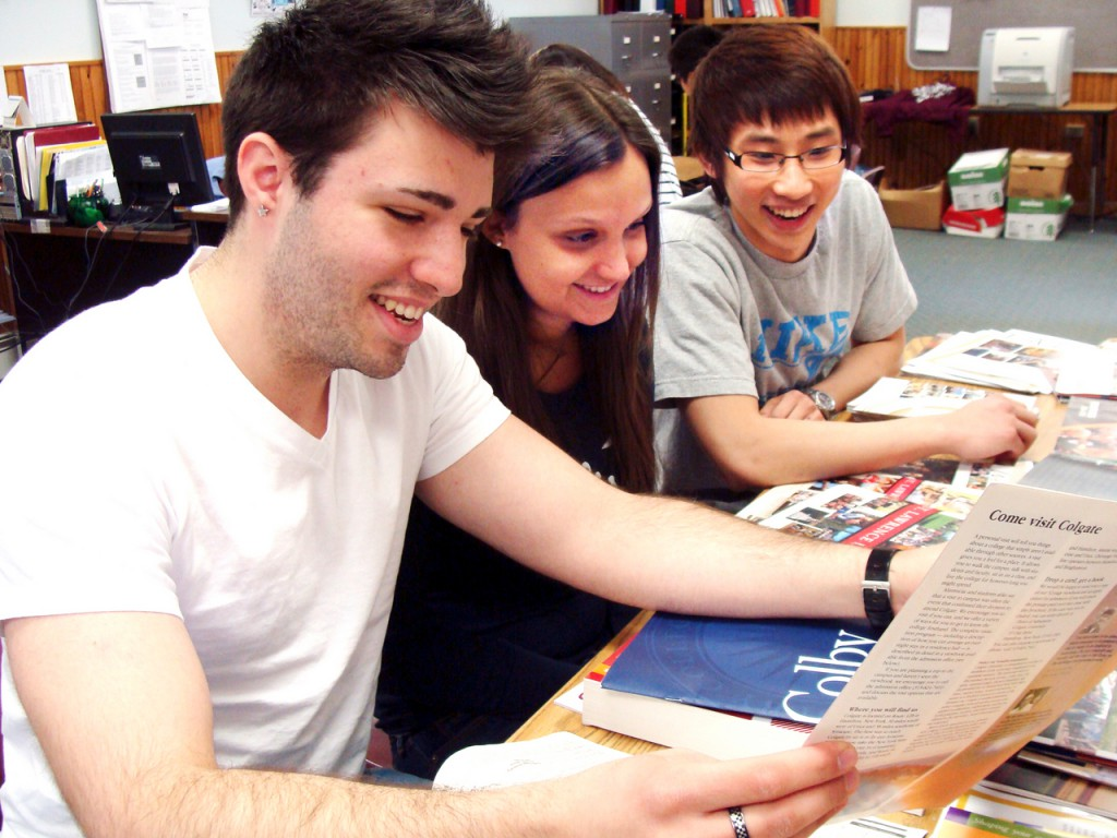 Adrien Simon of Paris, France, Priscila Muro of Sao Paulo, Brazil, and Fa Lin of Beijing, China, all boarding students at Foxcroft Academy in Dover-Foxcroft,  spent time Thursday looking over some college brochures. BANGOR DAILY NEWS PHOTO BY DIANA BOWLEY