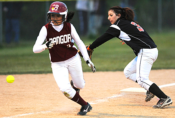 Brewer's Sarah Babin, left,  chases down the ball as Bangor's Jade Baumrind jumps off third base for a dash to home plate during 3rd inning action on Friday, May 14, 2010 at Brewer. The ball was called foul and Baumrind returned to third base.  BANGOR DAILY NEWS PHOTO BY KEVIN BENNETT