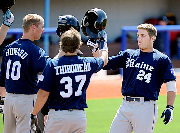 University of Maine's Justin Leisenheimer celebrates with teammates at home plate after hitting a 2-run homerun in the 6th inning to tie the game.  Maine beat Albany 4-2 in Sunday afternoon's game.  BANGOR DAILY NEWS PHOTO BY LINDA COAN O'KRESIK