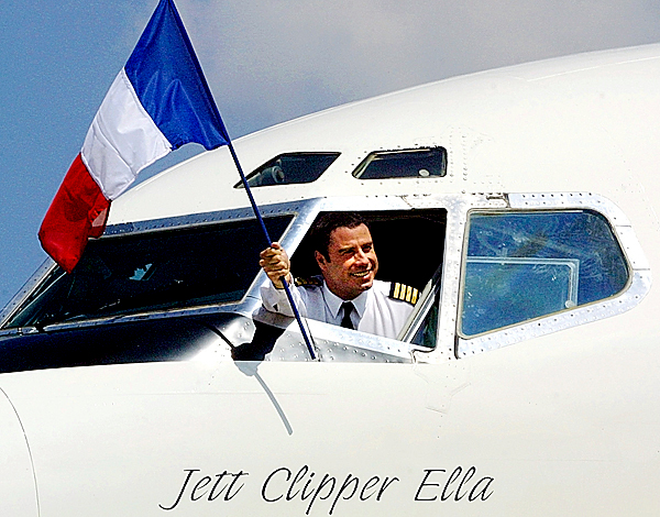 Actor John Travolta waves the French flag from the cockpit of his personal jet at Le Bourget airport outside Paris Tuesday, Aug. 13, 2002. Travolta, the Australian airline Qantas' &quotAmbassador-at-Large&quot, is on a global promotion for the Australian airline to show the airline industry in a positive light after the Sept. 11 terror attacks. (AP Photo/Jacques Brinon)