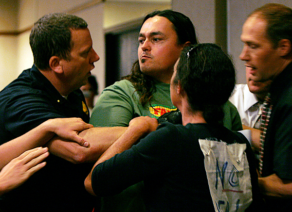 A protester, center,  is taken away by law enforcement officials after interrupting a meeting held by the Land Use Regulation Commission  in Bangor, Maine on Wednesday September 23, 2009. The Commission voted to approve Plum Creek Timber Co.'s plan to develop an area by Moosehead Lake. (AP Photo/Pat Wellenbach)