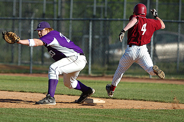 Hampden's Fred Knight (left) receives the throw as Bangor's Luke Hetterman (4) propels himself to first base in the fourth inning of Monday's game, May 17, 2010 at Mansfield Stadium in Bangor. The Rams went on to win 15-2. BANGOR DAILY NEWS PHOTO BY BRIDGET BROWN