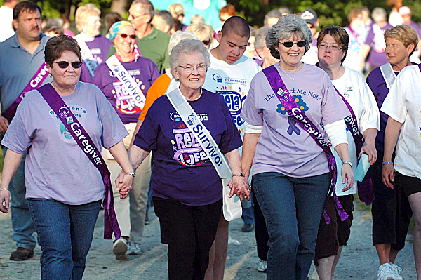 Cancer survivor Susan Oliver of Lee (center), walks hand-in-hand with her daughters Marge Louder of Corinna (left) and Janine Smith of Springfield during the opening lap of the Relay for Life at the Old Town High School track Friday, May 21, 2010. The event continues through today with 84 teams participating to raise money for the American Cancer Society.  BANGOR DAILY NEWS PHOTO BY BRIDGET BROWN