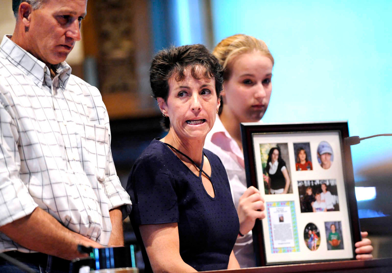Turning her eyes towwards Justin Ptaszynski (not pictured), Kathy Ingraham (center) of Old Town, mother of murder victim Holly Boutilier, makes an impact statement during Friday's plea and sentencing for Ptaszynski at Kennebec Supior Court in Augusta, Maine Friday, May 21, 2010. Stnading next to her is Holy Boutilier's father, Gene Boutilier of Oakfield and Holly's younger sister Sarah Boutilier, 18 of Old Town who was holding a photo collage of Holly Boutilier. BANGOR DAILY NEWS PHOTO BY JOHN CLARKE RUSS
