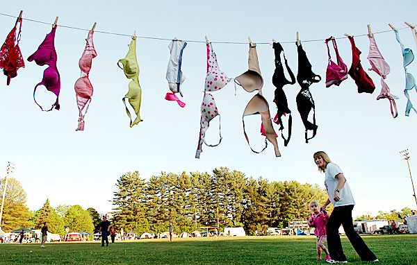 Debbie Miles and Aidriana Doane, 4, both of Milford, walk under a string of bras hung under a goalpost by Team Twitter members at the Relay for Life at the Old Town High School track Friday, May 21, 2010. According to team captain Audrey Brissette, the bras will be donated to Athena's Cup, an organization raising money and bras to fight breast cancer, which is trying to break the record of 169,000 bras for world's longest chain. (Bangor Daily News/Bridget Brown)